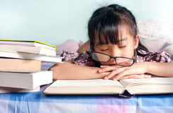 Asian child sleeping while reading in the bed. girl with glasses Stock Images