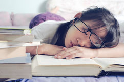Asian child sleeping while reading in the bed. royalty free stock photos