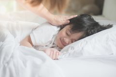 Asian child sleeping on white bed. Cute Asian child sleeping on white bed with mother care Royalty Free Stock Photos