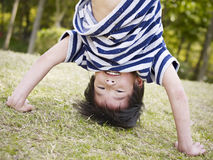 Asian child standing on hands outdoors Royalty Free Stock Images