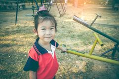 Asian child standing near seesaw at children playground. Vintage Royalty Free Stock Photography