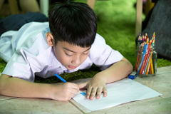 Asian child in student uniform painting on a white paper Stock Photography
