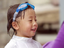 Asian Child after Swimming. An Asian child happily smiling after swimming, hair and face wet, wearing blue swim goggles on head Royalty Free Stock Image