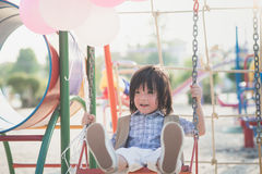 Asian child on a swing on summer day. Happy Asian child on a swing on summer day stock image