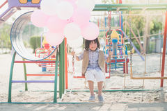 Asian child on a swing on summer day. Happy Asian child on a swing on summer day Royalty Free Stock Photography