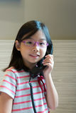 Asian child talking on the phone. Portrait of Asian little girl speaking on the phone Stock Images