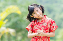 Asian child in traditional Chinese cheongsam with nature backgro Stock Photos