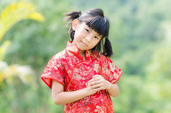 Asian child in traditional Chinese cheongsam with nature backgro Royalty Free Stock Photography