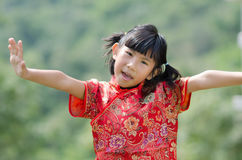 Asian child in traditional Chinese cheongsam with nature backgro Royalty Free Stock Images