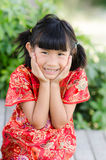 Asian child in traditional Chinese cheongsam with nature backgro Stock Photo