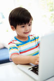 Asian Child Using Laptop At Home Stock Images