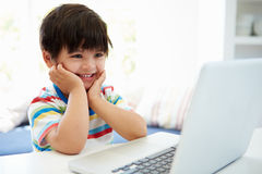Asian Child Using Laptop At Home Royalty Free Stock Photography