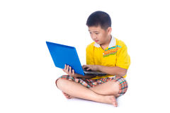 Asian child using a laptop, sitting on white background, isolate Stock Photos