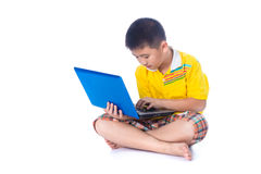 Asian child using a laptop, sitting on white background, isolate Royalty Free Stock Photos