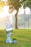 Asian child watering plant outdoors. Royalty Free Stock Photos