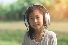 Asian child wearing headphone with bokeh Royalty Free Stock Images