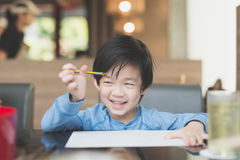 Asian child writing on white paper. Cute Asian child writing on white paper Stock Image