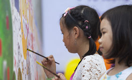 Asian children drawing images and writing their wishes. Hanoi, Vietnam - Sep 19, 2015: Asian children drawing images and writing their wishes by paint brush on a Royalty Free Stock Photos