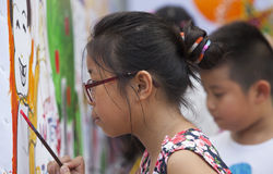 Asian children drawing images and writing their wishes. Hanoi, Vietnam - Sep 19, 2015: Asian children drawing images and writing their wishes by paint brush on a Stock Photography
