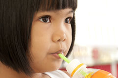 Asian children drinking water. Portrait of a little Asian girl in drinking water Stock Image