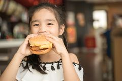 Asian Children eat chicken cheese Hamburger Food Court.  stock photo
