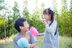 Children eating cotton candy in park together Royalty Free Stock Photo