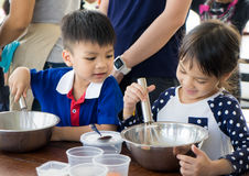 Asian children enjoying educational cooking class. They making homemade ice cream with family. Homemade baking and cooking with family help child develop Stock Photography