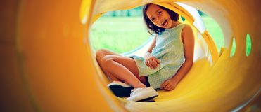 Asian children happiness and happy girl concept. A little girl sitting in the tube-playground and her is smiling Stock Image