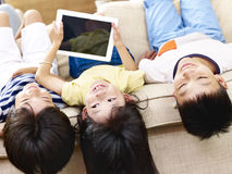Asian children having fun at home. Three asian children having fun lying upside down on couch stock images