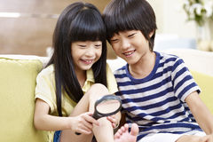 Asian children having fun with a magnifier. Two asian children sitting on couch at home having fun playing with a magnifying glass Royalty Free Stock Photo
