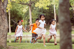 Asian children having fun to run and play together. In the park in vintage color tone Royalty Free Stock Images