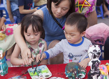Asian children painting and writing their wishes on wishing cards. Hanoi, Vietnam - Sep 19, 2015: Asian children painting and writing their wishes on wishing Royalty Free Stock Photos