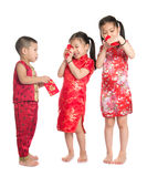 Asian children peeking into red packet. During Chinese New Year, with traditional Cheongsam full length standing isolated on white background Stock Photography