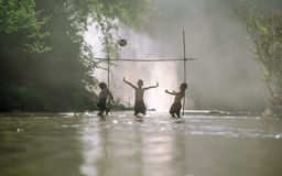 Asian children play soccer in the river,Sport plays an important