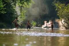 Asian children play soccer in the river,Sport plays an important. Role in rural and regional Thailand,Sport are the predominantly or exclusively played in rural royalty free stock photo