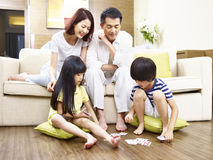 Asian children playing cards while parents watching Stock Photos