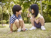 Asian children playing with magnifier outdoors Stock Image