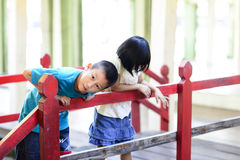Asian children playing on red wooden bridge. Stock Photos