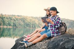 Asian children playing tablet in nature. Relax time on holiday concept travel,selective and soft focus,tone of hipster style stock photography