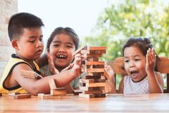 Asian children playing wood blocks stack game together with fun. And excited when it falling royalty free stock images
