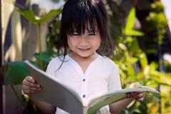 Asian children reading a book in home garden Royalty Free Stock Photos
