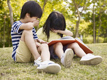 Asian children reading book outdoors. Little asian boy and girl sitting on grass laughing while reading a book, outdoors in a park Royalty Free Stock Photography