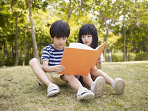 Asian children reading book outdoors Stock Photos