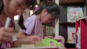 Children`s little girls studying lessons at home.