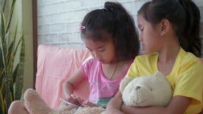 Children`s little girls using smart phone at home.