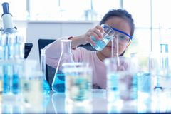 Asian children Scientists analyzing study evaluating microscope. Health care researchers doing some research with dropper chemical. Testing and working in life stock photo