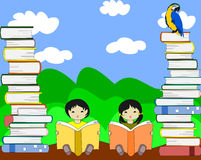 Asian children sit among piles of books and reading Royalty Free Stock Photo