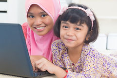 Asian children surfing internet. Southeast Asian children surfing internet at home. Malay Muslim girls royalty free stock images