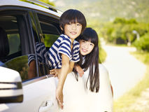 Asian children traveling in a car. Happy asian little boy and girl sticking their heads out of car window stock image
