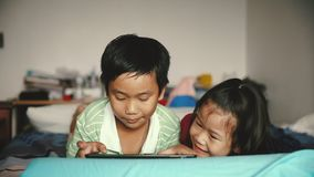 Asian children using digital tablet. Cinematic tone. Asian children using digital tablet. Happily sister hugging and cheering her brother. Cute boy playing stock footage